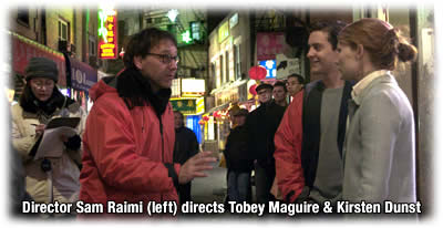 Director Sam Raimi (red jacket) directs Tobey Maguire and Kirsten Dunst
