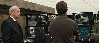 Bruce Wayne (Christian Bale) and Alfred (Micheal Kane) review video footage of their new nemesis.